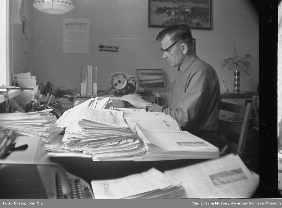 Redaktøren av Nuorttanaste John Ole Nilsen hjemme i stua si i Bunes i full gang med å sveive adressemaskinen med abbonentene til bladet. Mange eksemplarer av Nuorttanaste ligger på skrivebordet og venter på å bli adressert og sendt ut. 1967.