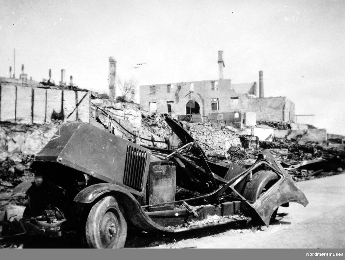 Bilen er en Renault fra 1920-tallet, med radiatoren montert bak motoren.(Info: Ivar Stav).  -Andre verdenskrig har kommet til Kirkelandet i Kristiansund. Her ser vi fra ruinene av Clausengården fra Storkaia, med et bilvrak i forgrunnen. Meieripipa bak th. Bildet er datert 28. april 1940, som er samme dag som byen ble bombet for første gang. serie. Fra Nordmøre museums fotosamlinger.
