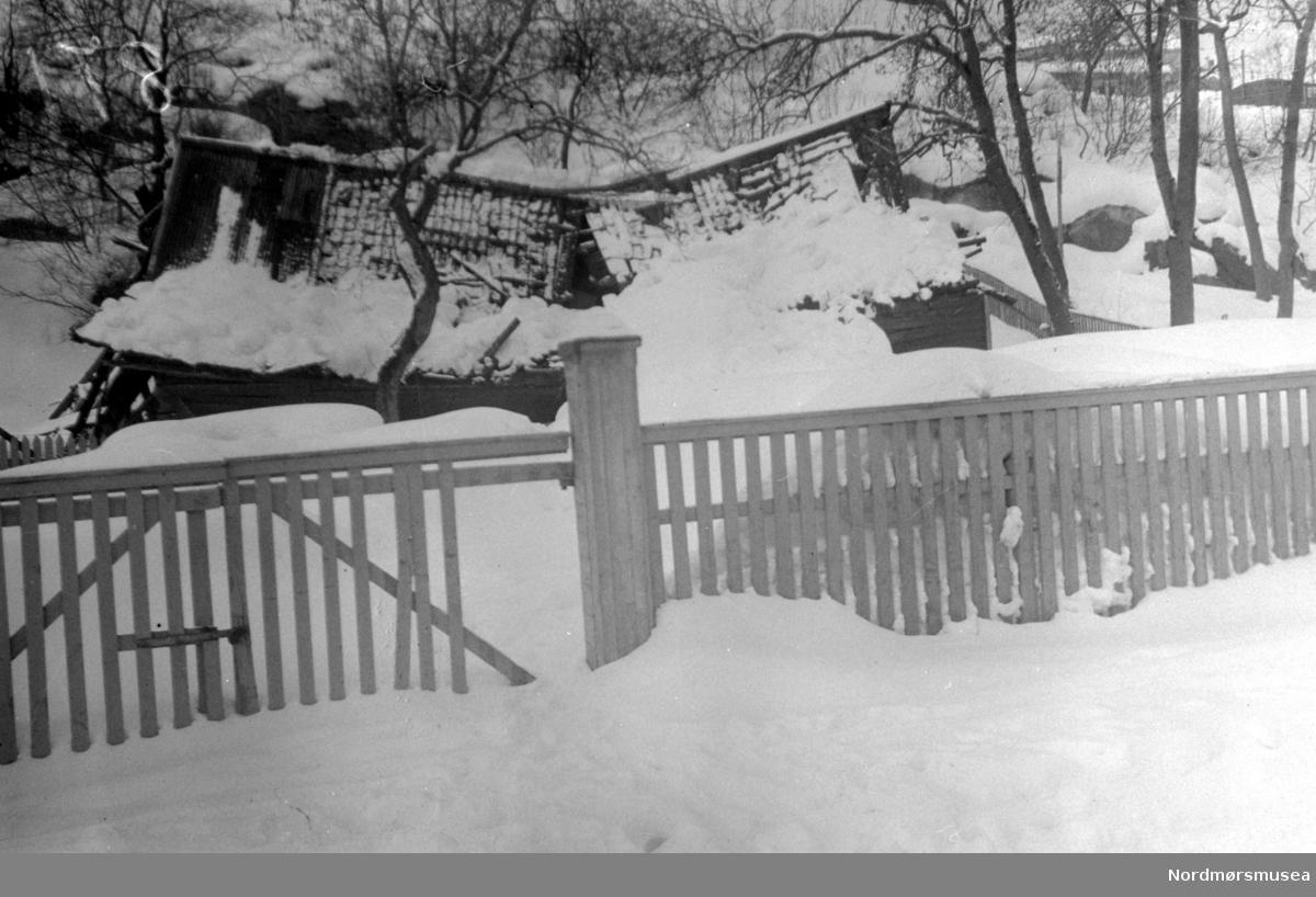 På bildet ser vi ruinene av fjøset på Johnsengården i Vågen. Bildet er tatt fra øst i Fosnagata, 16. mars 1947. Fjøsbygningen var opprinnelig til den gamle kjøpmannsgården. Da fjøsholdet oppørte i 1880-årene, ble bygget brukt til lagerplass på gården. Ved havnevesenets overtakelse av Johnseneiendommen omkring 1930, ble fjøset brukt til lager for utrangerte gjenstander tilhørende byens offentlige verk. Men under den voldsomme snø- vinteren 1946-1947 brakk taket sammen under de tunge snømassene 16. mars 1947. Mer informasjon kan finnes i Yderstads notater, bind 3, side 51. Se også bilde fra det samme fjøset på 1947/880 (KMb-1947-000.0880.jpg). Fra Nordmøre Nordmøre Museums fotosamlinger