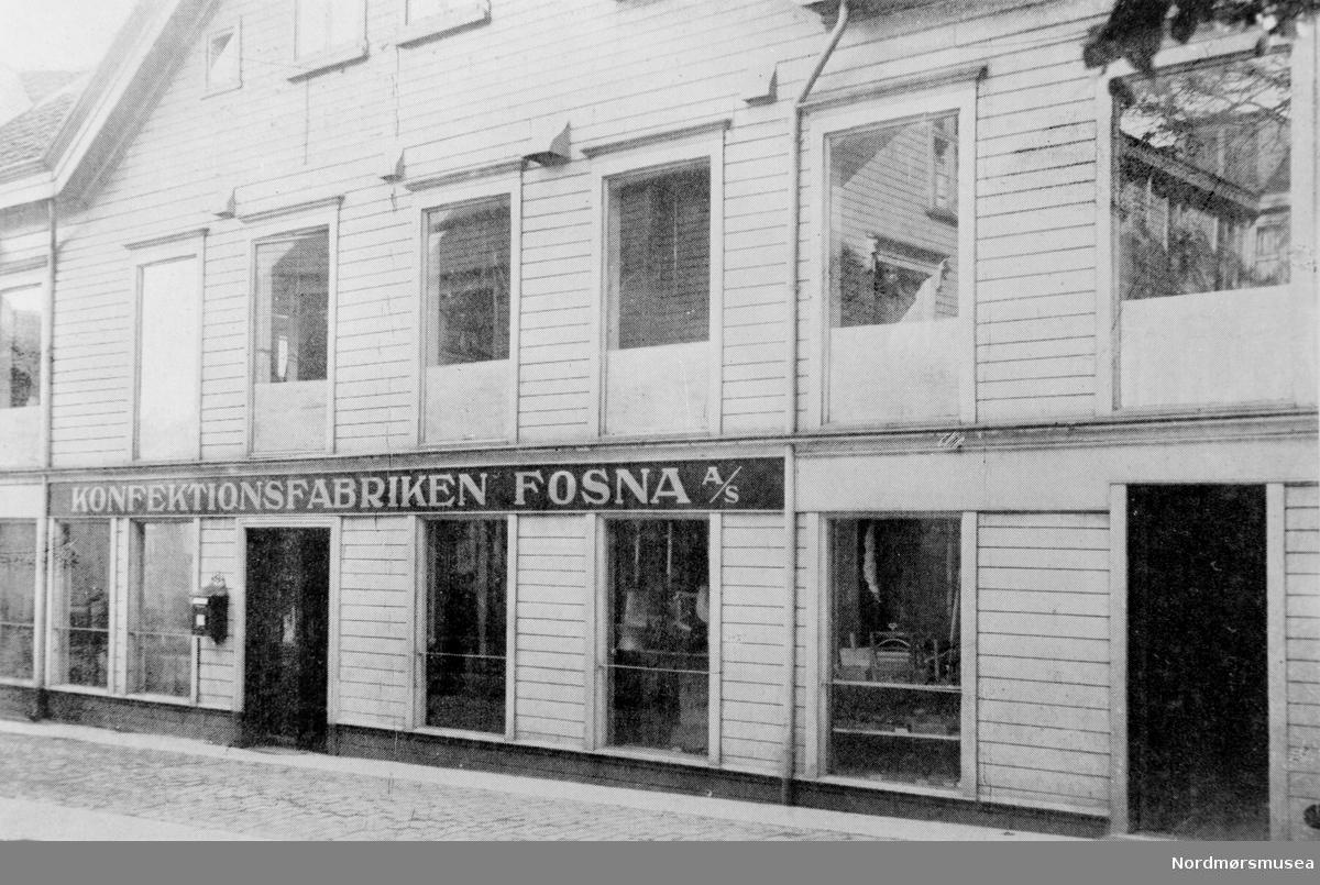 """"""";Konfektionsfabriken Fosna A/S""""; Konfeksjonsfabrikken Fosna AS ble startet høsten 1913 av Oluf Herlofsens sønner. Senere utvidet fabrikken til å omfatte herrekonfeksjon som vinterfrakker og dresser med mere. Da bedriften under krigsårene fikk et ganske betydelig omfang, ble den i 1919 skilt ut fra hovedfirmaet og gikk over til eget aksjeselskap med en innbetalt aksjekapital på kroner 275.000 som senere ble økt til 325.000 kroner. Fabrikken ansatte ca. 50 personer i verkstedlokalene, foruten tilskjærere, kontrollører og kontor- og lagerpersonale. Datering er trolig omkring 1928. Fra Nordmøre museums fotosamlinger."""