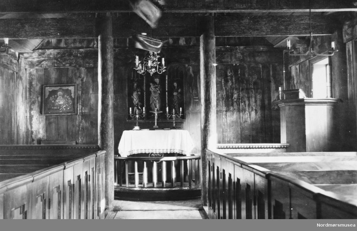 """På bildet ser vi fra interiøret i Grip stavkirke.  Her ser vi fra benkradene på hver side, med alterringen, altertavlen samt altret med den hvite alterduken, lysestaker og krusifiks. Når det kommer til den sengotiske altertavlen med gotisk fletteverk og renessanse-rundbuer, ser en disse figurene fra venstre til høyre, utført i tre: 1.) Sankt Olav med rikseple i venstre og øksen i høyre hånd, som tråkker på en syndens figur, en drageaktig skikkelse, med menneskehode dekket av en turban (arketypen """"tyrkeren""""). 2) Jomfru Maria med barnet på armen. 3.) St. Margaretha (på Grip kalt """"Maret"""") - en ung kvinne med to lange fletter i buer. Et hunde- eller ulvehode stikker frem foran føttene hennes. Til venstre finner vi inngangen til sakristiet.  Litteratur: Tone M Olstad: Alterskapet i Grip stavkirke, NIKU Rapport 5, 2003. Jostein Iversen: Grip, 1998. Samt www. stavkirker.org. Fra Nordmøre Museums fotosamlinger. variant"""