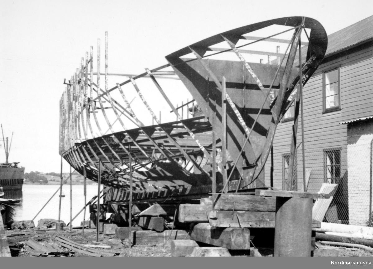 """Foto av bygg nr. 13 - sundbåten """";kvikk""""; - under produksjon ved A/S Stord Verksted i Bergen. Båten ble bygget i 1950/1951 ved A/S Stord Verksted i Bergen, etter at det ble inngått kontrakt 14. april 1950. Prisen ble satt til 109.000 kroner og endelig kjøpsum ble 117.374 kroner. Båten ble sjøsatt 11. november 1950, og kom til Kristiansund 14. februar 1951, for å bli overlevert den 15. februar 1951. Kvikk var 14,1 meter lang, 3,7 meter bred og veide 24,9 bruttotonn og var utstyrt med en 6 sylindrer 4 takts Lister diesel med 62 HK. Båten skulle bli en problembåt og hadde flere motorhavarier. På styremøtet 27. september 1965 ble det besluttet og selge Kvikk sammen med sundbåten Presto til Erling Halle i Todalen, for 11.000 kroner. Etter en periode i opplag i Skålvik-fjordenm ble så Kvikk ombygd til slepebåt ved Årsund mekaniske verksted og ble omdøpt til Tug Odin for så å bli satt inn i isbryting frem til 1980. Ble så solgt videre til et dykkerfirma i Bergen, og siste kjente tilholdssted er et oppdrettsanlegg i Nord-Troms. Giver er Kristiansunds havnevesens fotosamling, nå i Nordmøre Museums fotosamlinger.  Kilde: Sven Erik Olsen og Tor Olsen. Sundbåten. Folk over havna - fra fergemenn til Angvik. Utgitt 2005. /Reg:EFR2013/"""