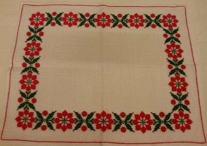 Duk broderad i korstygn med röd och grön lingarn på vit linneväv. fållad i stjälkstygnsrand 1cm från ytterkant.