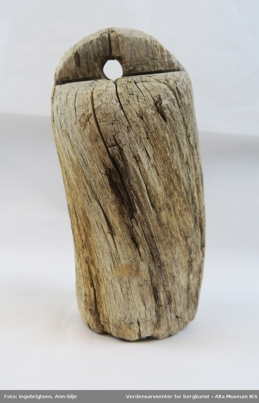 Sylinderformet trekubbe med halvsirkelformet kant på toppen. I kanten er det hull i midten til å tre halsbåndet i gjennom.