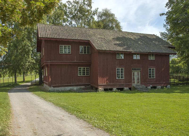 Stor, rød, plankebeslått bygning i to etasjer. (Foto/Photo)