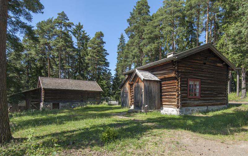 Husmannsplass med brunlig hus i halvannen etasje og med tilbygd vindfang, og en gråbgun tømmerlåve med utedo ved siden av. (Foto/Photo)