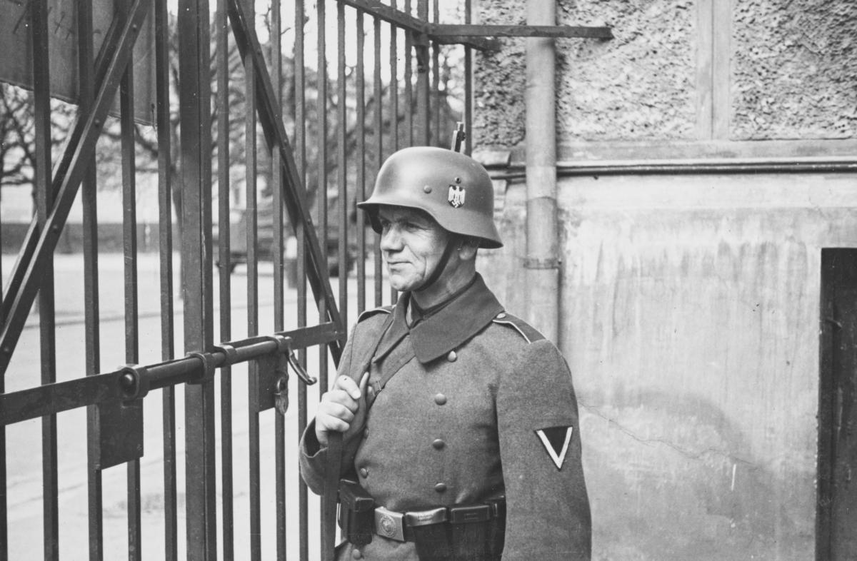 Norsk fangeleir  ved Logen i mai 1940. Tysk vakt ved porten.