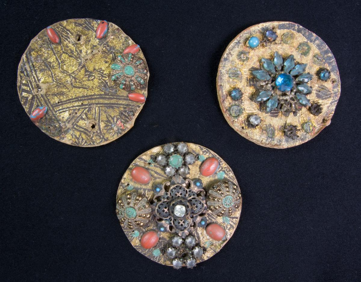 Smycke, 3 st, runda av guldmålad papp med glasbitar, knappar med mera fästade med metalltenar samt klistrade på pappskivorna.