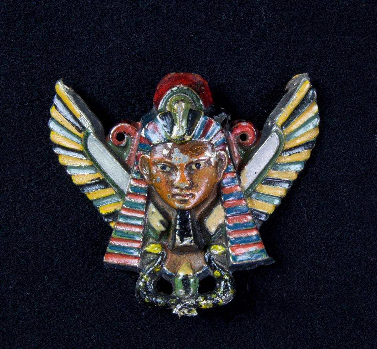 Beslag av vitmetall i egyptisk stil i form av en farao, fågel med utbredda vingar och två ormar i rött, grönt och gult. Två hål att fästa på klädesplagg.