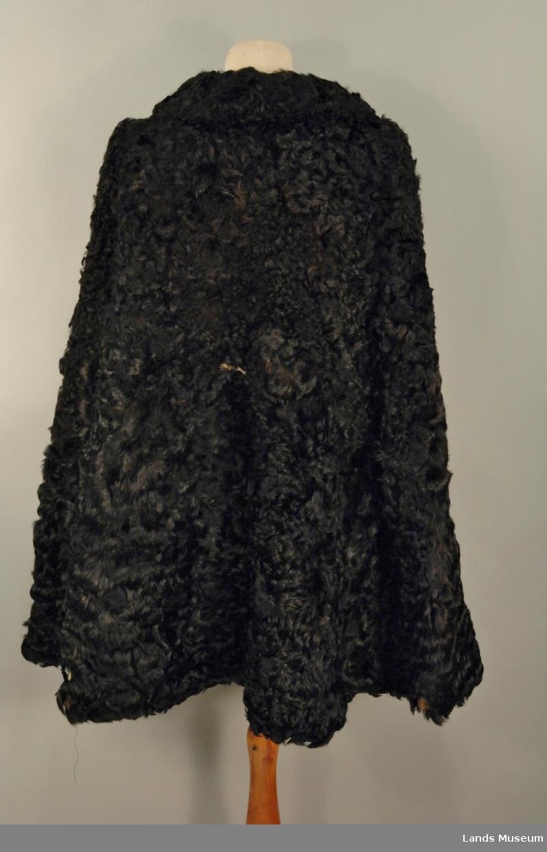 Vid cape, rekker ca. til hoften, store hekter framme, 6 stk. Tykt svart satengvevd natursilkefor. Lommer på innsiden.