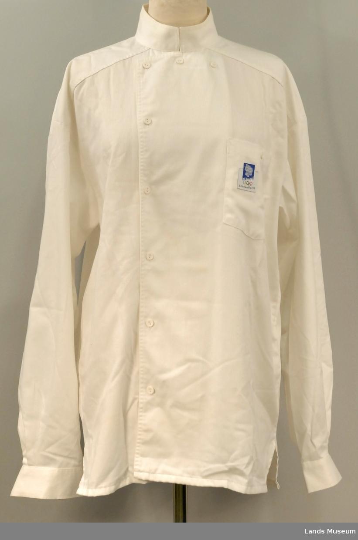 Skjorte med knapping påhøgre side. Tre knapper øverst. Striper i stoffet. Skulderstykke, rynking av bakstykke mot skulderstykke.