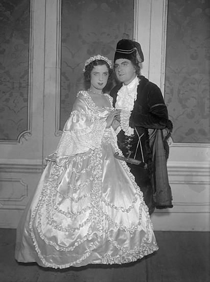 """Scen från operetten """"Tiggarstudenten"""". En man med hatt i 1700-talsdräkt och en kvinna i balklänning."""