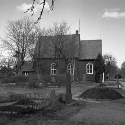 Foto av en (mindre) träkyrka med kyrkogård. Tutaryd.