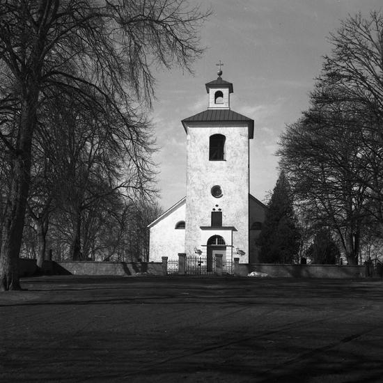 Stenbrohults kyrka. 1951.   Ett ritningsförslag till ny kyrkobyggnad i Stenbrohult utarbetades 1807 av Henrik Måsbeck vid Överintendentsämbetet. Det dröjde dock till 1827 innan det slutliga beslutet om nybyggnad togs. Kyrkan uppfördes 1828 – 1830 i empirestil och invigdes 2 juni 1833 av biskop Esaias Tegnér. Kyrkan består av långhus med kor i väster och kyrktorn i öster.Tornbyggnaden är försedd med en öppen lanternin med tornur krönt av en korsglob. Väster om koret ligger en sakristia med avfasade hörn. Kyrkan är uppförd i sten, putsad och vitkalkad.