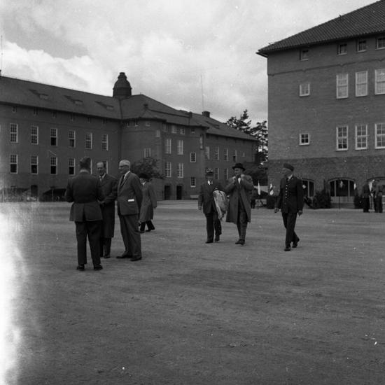 Foto av flera män i rock och hatt  på kaserngården till I 11, Växjö.