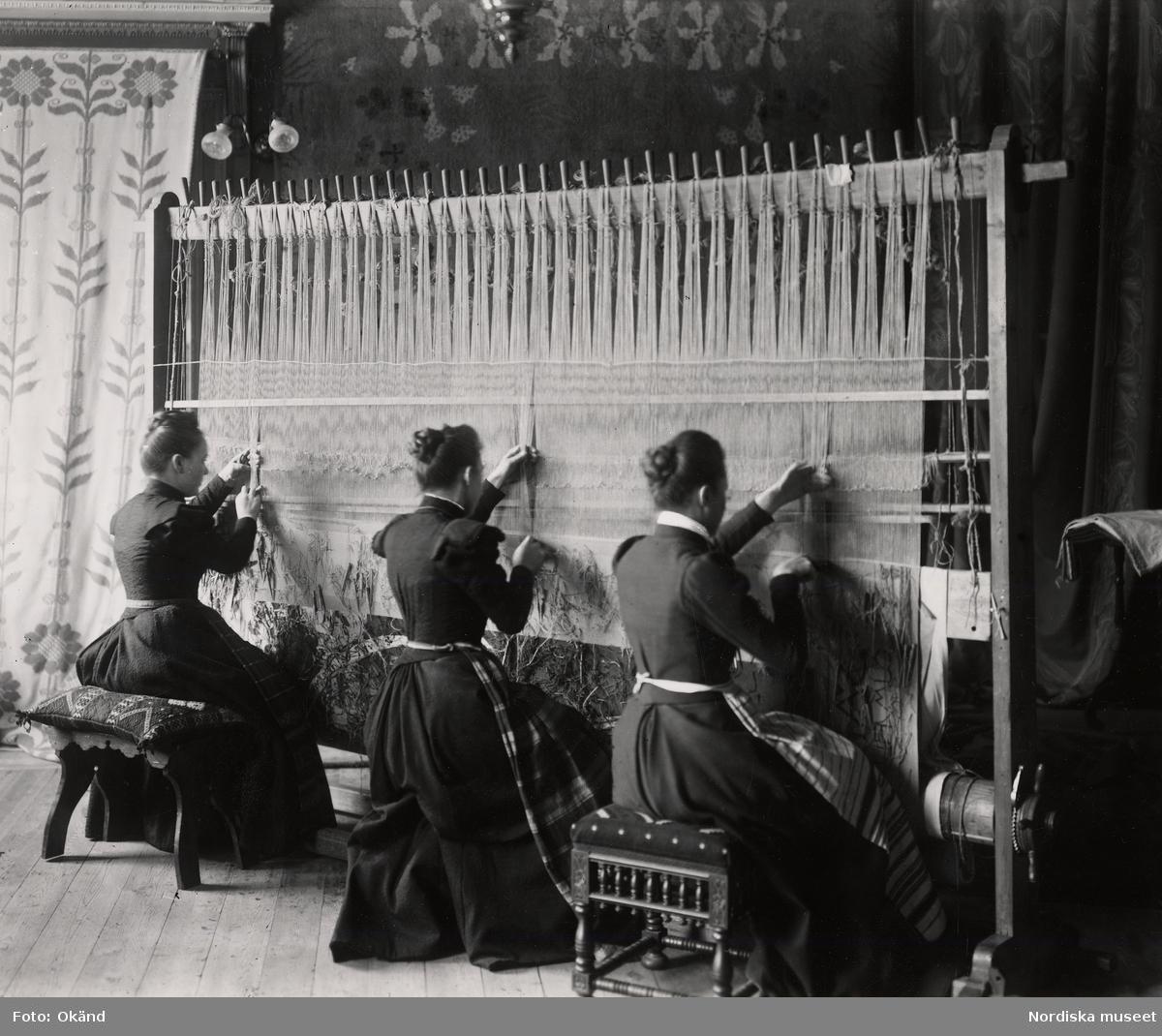 Tre kvinnor med uppsatt hår sitter vid en stående vävstol och väver. Handarbetets Vänner.