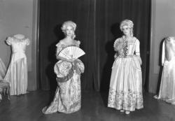 Ett grupporträtt med två kvinnor i klänningar från 1700-tale