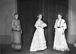 Ett grupporträtt med tre kvinnor.Till vänster syns en kvinn