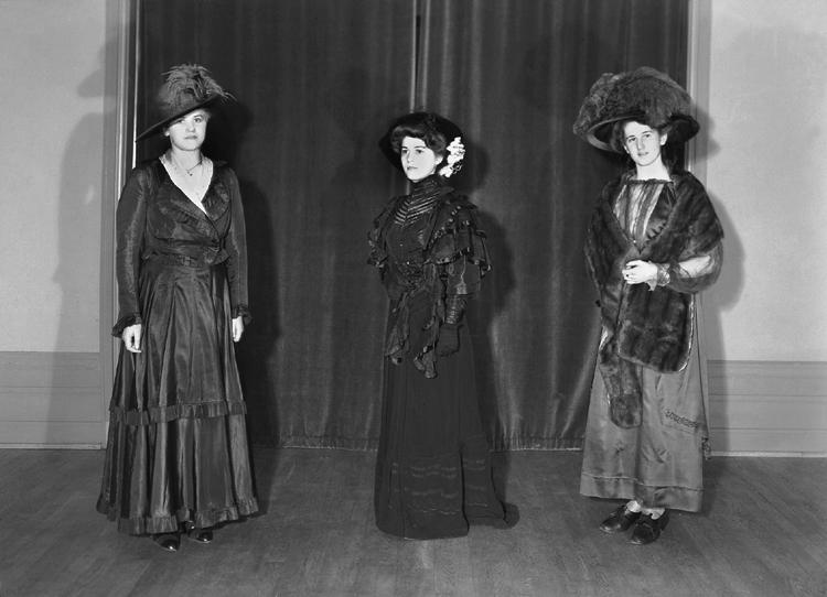 Ett grupporträtt med tre kvinnor i klänningar och hattar från ca 1910-1914.