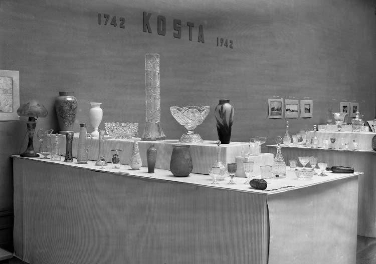 Foto av glasutställning i  Smålands museum.Man ser ett antal bord med jugendglas m.m.