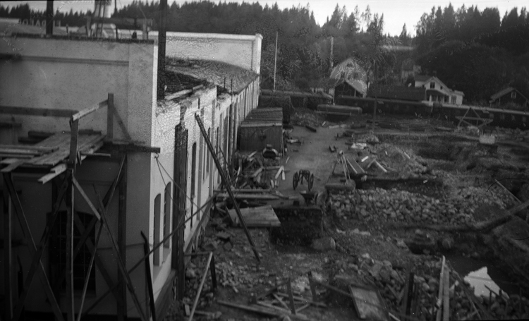 Foto på en fabrik med en byggställning mot fabriken.