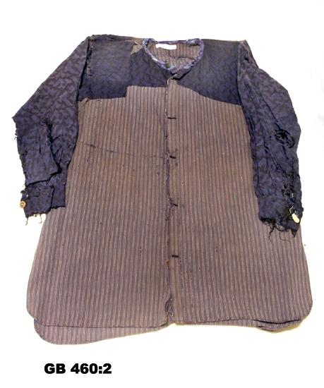 Arbetsskjorta. Hemsydd. Rak modell med ståkrage, långa ärmar med manschett. Blårandig, troligen handvävt tyg. Lagad med många  olika sorters tyger: blommigt, prickigt, enfärgat. Många olika sorters knappar. Damskjorta ?   Inskrivet i huvudkatalogen 1996-1997. Funktion: Arbetsskjorta