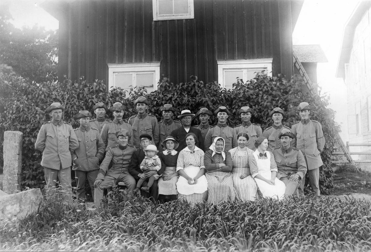 """Från vänster: plantare från Ljusne, Hans Larsson från Lilltjära i Hanebo. Mannen i ljusa hatten är Skinnar-Pelle (Hansson), kvinnan med ljusa huvudduken är hans fru Marta, omedelbart till höger om henne sitter Ella Olsson som var syster till Skinnar-Pelle, stående näst längst till höger är Lars Olsson från Rengsjö och ytterst Lundeberg från Gävle. Sittande från vänster: Gunnard (befäl), Evert Svedlund med Skinnar-Jonas i knät. Jonas var född 1913. Militärerna som bevakade järnvägsbron bodde i Ol-Ers och åt i Skinnars. I bakgrunden Skinnars """"gammelbyggning"""", som numera är riven. Till höger skymtar nuvarande boningshuset. Bilden troligen från 1916."""