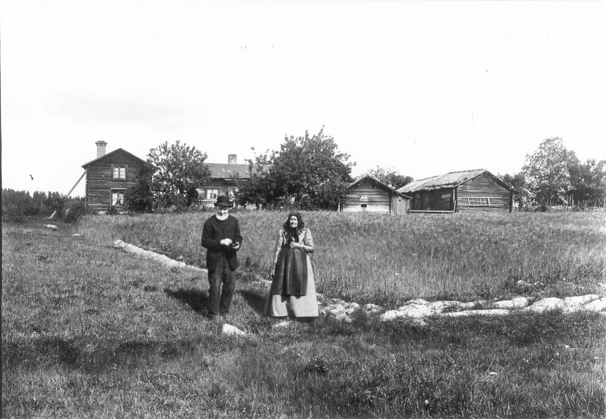 Äldre par framför gård.