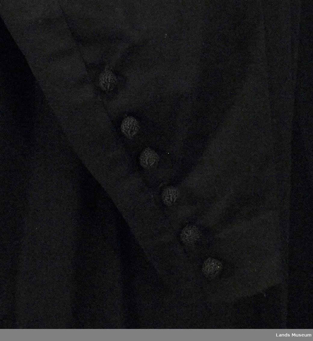 Tøy av fint kjoleklede. Kjolen er helklipt. Forstykket er rynket inn i skuldersøm. V-formet halsåpning med krage som går i ett med belegg i forkant og som har svakt butte spisser. Lukkningen foran er ca. 72 cm lang, har trykknapper og har 13 flettede kuleknapper. Flere knapper mangler. Ved bakre søm er det sydd på 6 kuleknapper. 5 cm fald nederst og 3 cm fald i ermene er sydd for hånd.