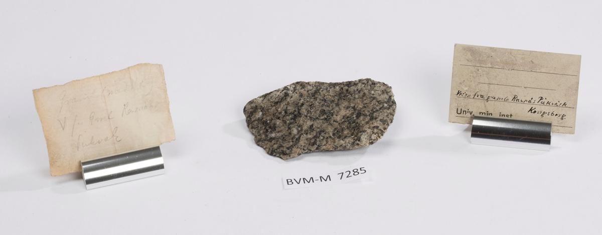 To etiketter i eske:  Etikett 1:  Granit (med H.b) V for Gml Ravnås Pukværk  Etikett 2: Veien fra gamle Ravnås Pukvärk. Kongsberg