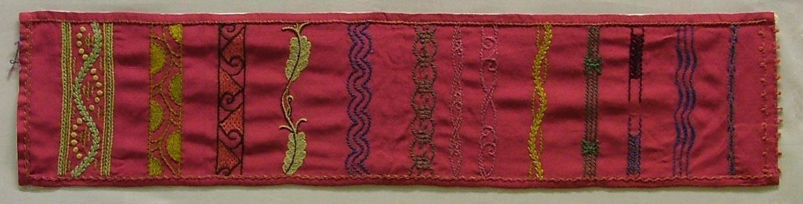 Tidigare katalogisering enl uppgift av Elisabeth Thorman:  Provlapp 74 x 17 med 14 st olika märkduks bårder på rött siden sydda i olika sömnader i silke. /387/