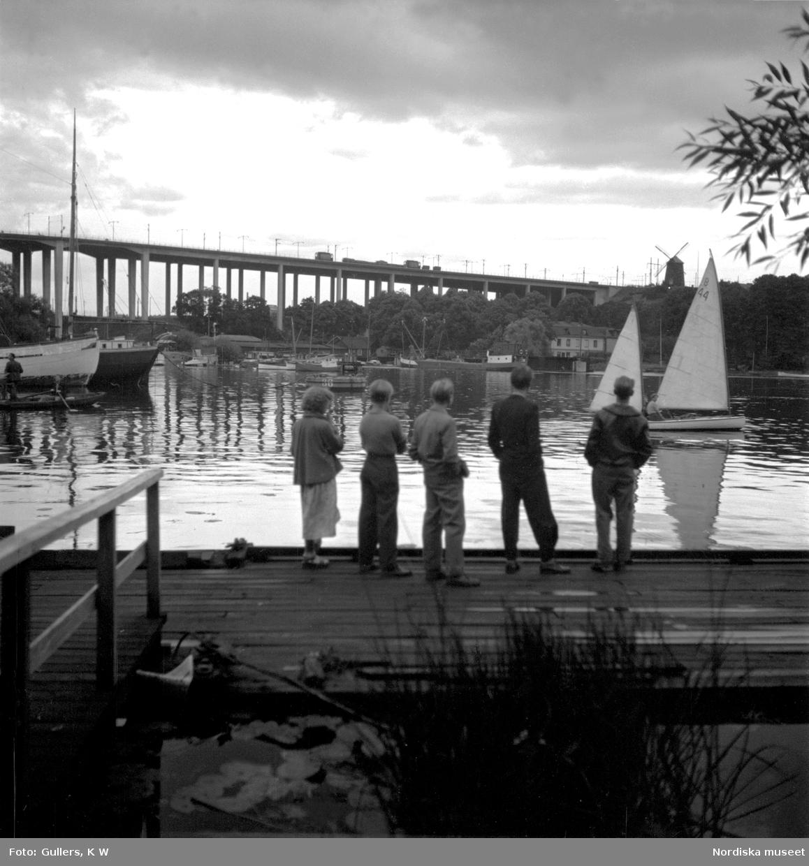 Södermalm, Stockholm. En grupp pojkar betraktar båtar på vattnet. Skanstullsbron i bagrunden.