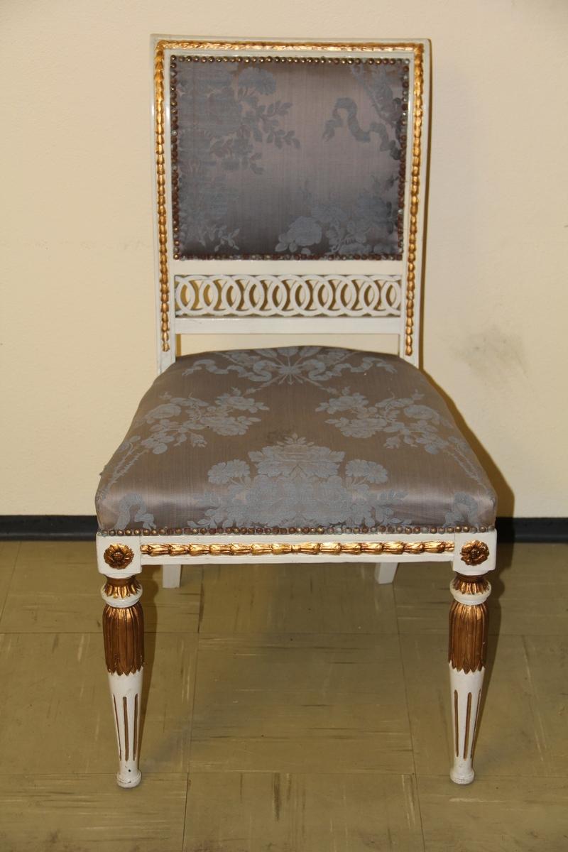 Stol i tre, stoff i sete og rygg. Stolpekonstruksjon. Louis Seize-elementer. Treverket er i hvitt og gull med utskjæringer. Blågrått trekk med mønster i ryggen. Malt på nytt av maler Kastrup i Mandal i 1945.