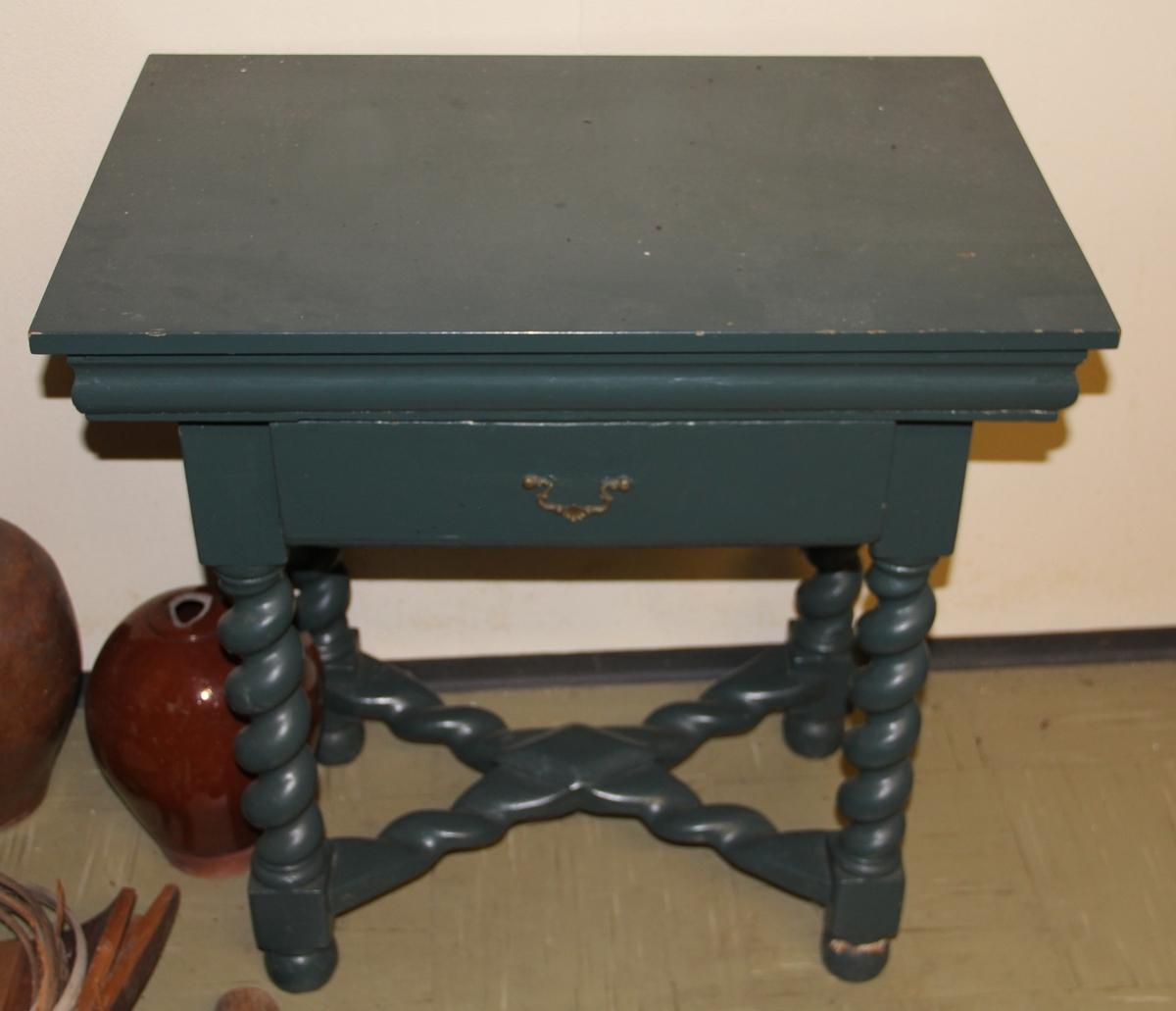 Brunt bord i tre med messingbeslag. Stolpekonstruksjon. Rektangulær form. Dreide bein. Blåbrun dekor under bordplata: Stjerne i sirkel med akantus rundt. Oppmalt i 1948.