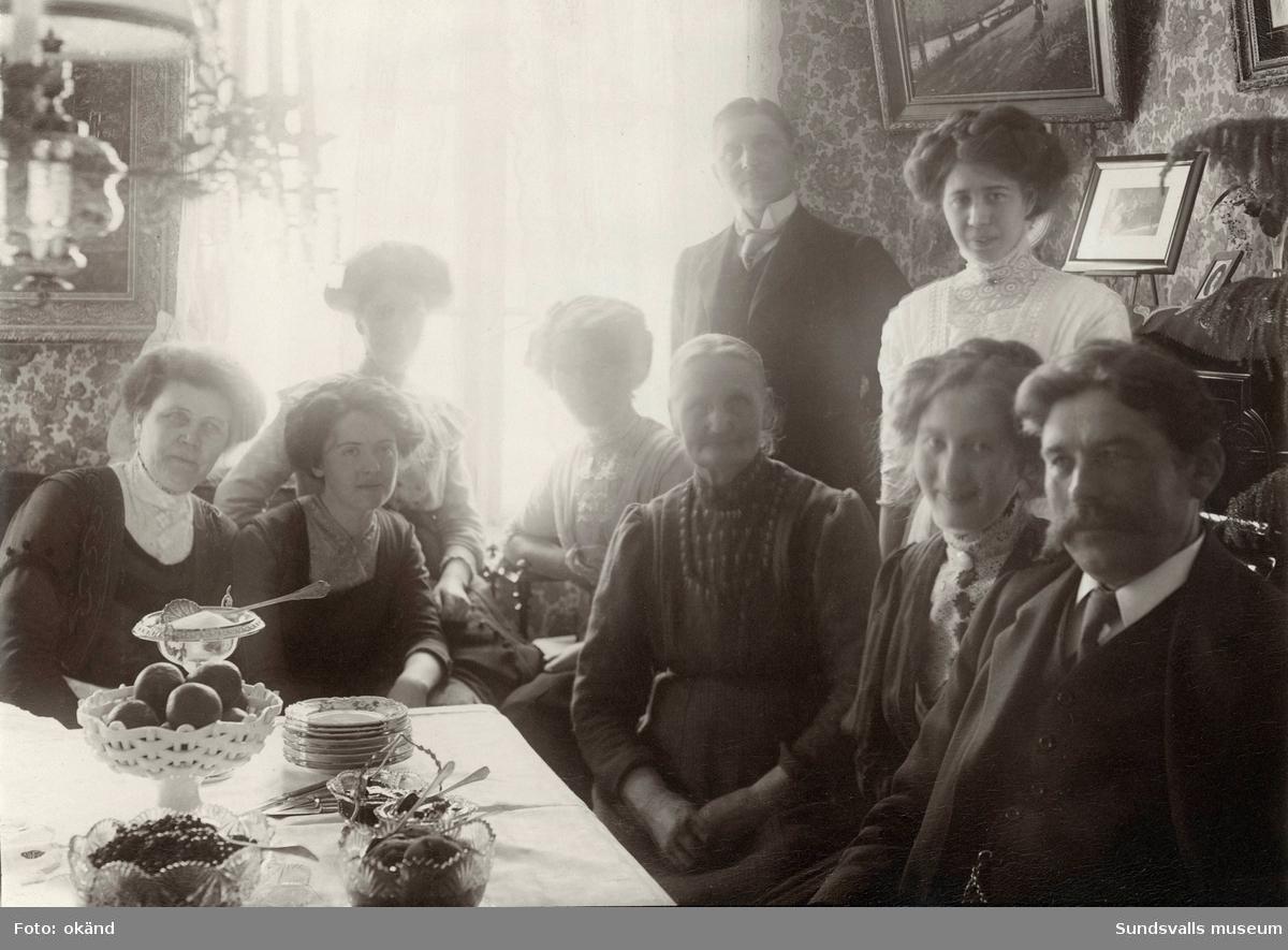 Stadsbarnmorskan Anna Hydén, sittande 3:a från höger, med delar av familjen samt bekanta. Dottern Anna ( d y) sitter 2:a från höger. Ester Gustafsson står ovanför Anna vid tavlan. Dottern Rut sitter 2:a fr vänster. De är samlade i bostaden på Skepparegatan 12, Norrmalm.