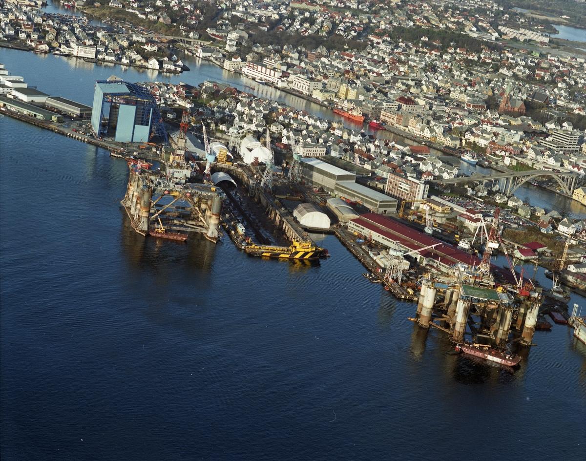 """Flyfoto. H.M.V. Oversikt over veftområdet med """"Nordsjøhallen"""". Hallen ser nesten ferdig ut fra utsiden. Odeco platformen """"Ocean Liberator"""" ved kai."""