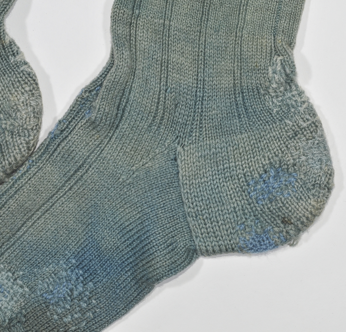 Strømpe, lang heimestrikka strømpe i blågrønt ullgarn. Pedant til VFF 6431. Strikka 6 rette og to vrange . Stoppet  mange plassar i foten.