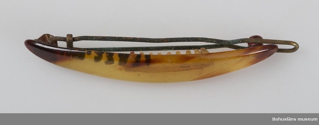 Oval, böjd form med taggar på insidan samt låsspänne av mässing. Ljusbrun genomskinlig färg med mörkare partier. Två bitar vitt bomullssnöre runtom.