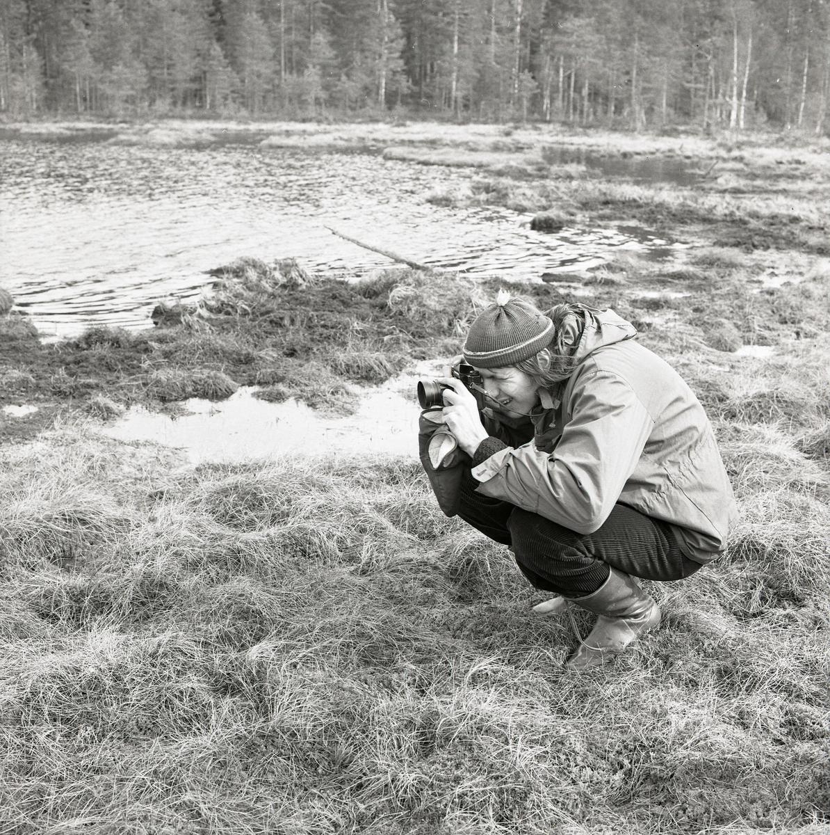 En man sitter på huk i gräset med kameran i högsta hugg. Han håller kameran intill sitt öga medan han justerar fokus genom att vrida på linsen med handen. Han är klädd i en tunn jacka, stövlar och mössa. Bakom honom sträcker Häggtjärnen ut sig och blåsten gör ringar på vattnet.