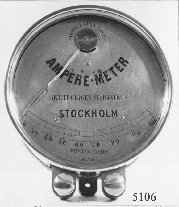 Amperemätare. Funnen på vinden av arbetsgrupp 1A,  ÖVK.  Av mässing, cylindrisk. Tavlan är graderad 0 - 100 mm. Märkt: Amperemätare Aktiebikaget Mekanikus Stockholm Wikholms system. Har troligen tillhört sågen vid snickarverkstaden.