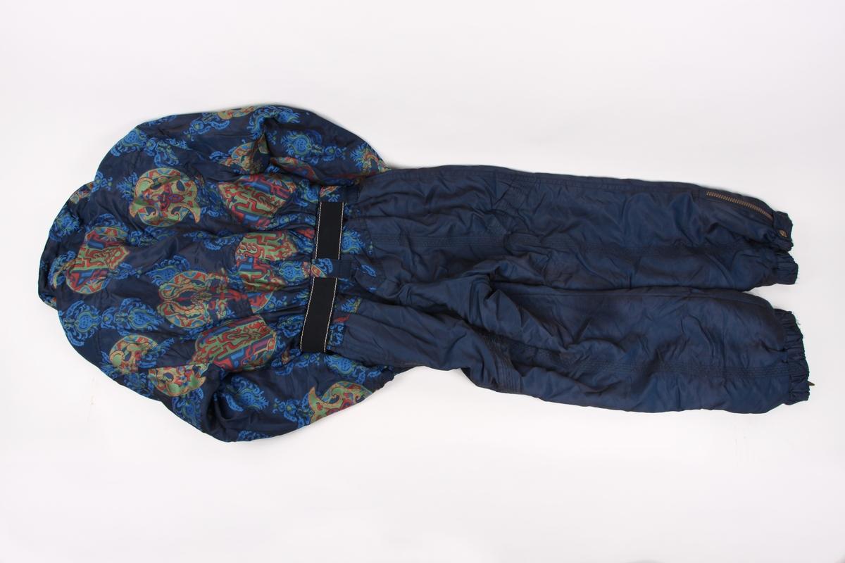 Hel alpindresss i størrelse 40 med skulderputer, glidelås og knapper foran, samt belte i livet. Dressen har tilhørende votter.