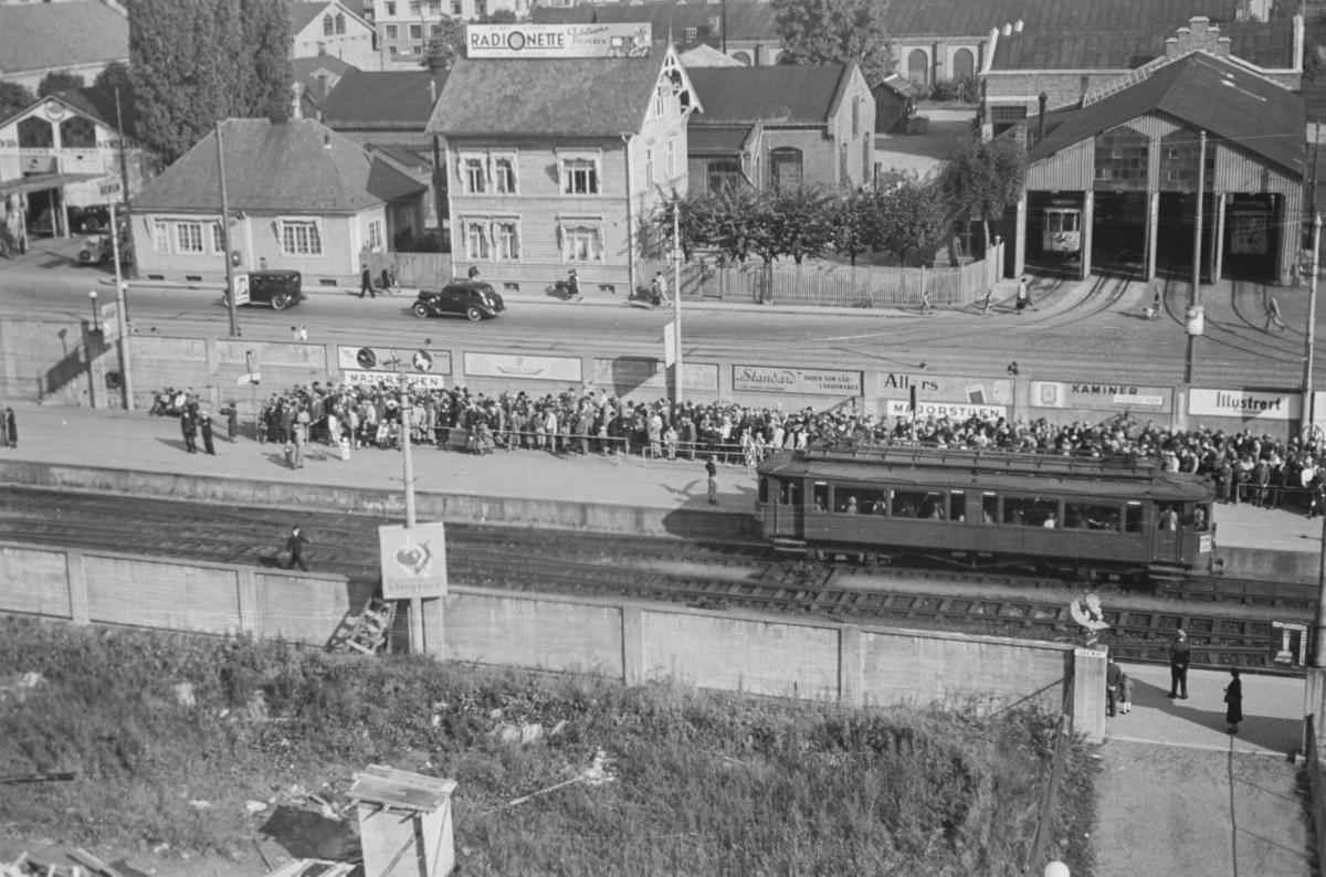 Stor trafikk på Majourstuen stasjon. Nordisk mesterskap i fotball ble arrangert på Ullevål stadioen, og denne dagen spilte Norge mot Danmark. Kampen endte 1-1. I forgrunnen sees en av Holmenkollbanens vogner i serien 31-37 - også kalt «trunk».