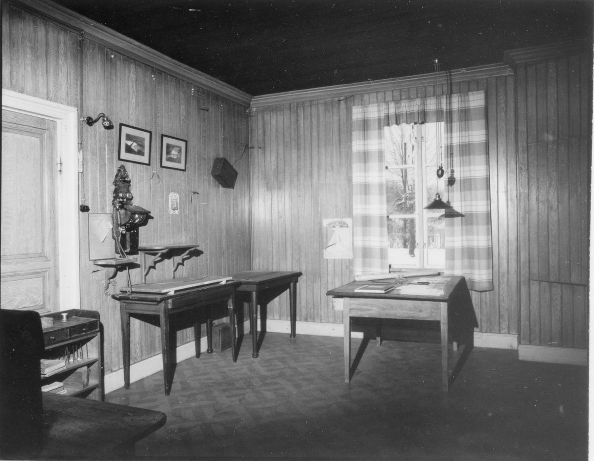 Gamla brukskontoret, Inspektorrummet.  1 st hylla, 2 st bord, 1 st inspektbord, 1 st telefon, 2 st fotografier, 1 st batterilåda till telefon (norr och öster vägg) almanacka.