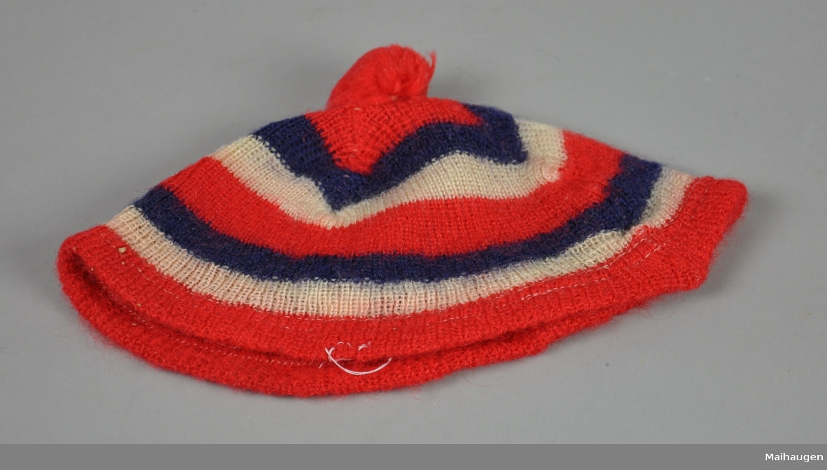 Lue med blå, hvite og røde striper. Dusk på toppen. Dusken er litt løs, holdes på plass med sikkerhetsnål.