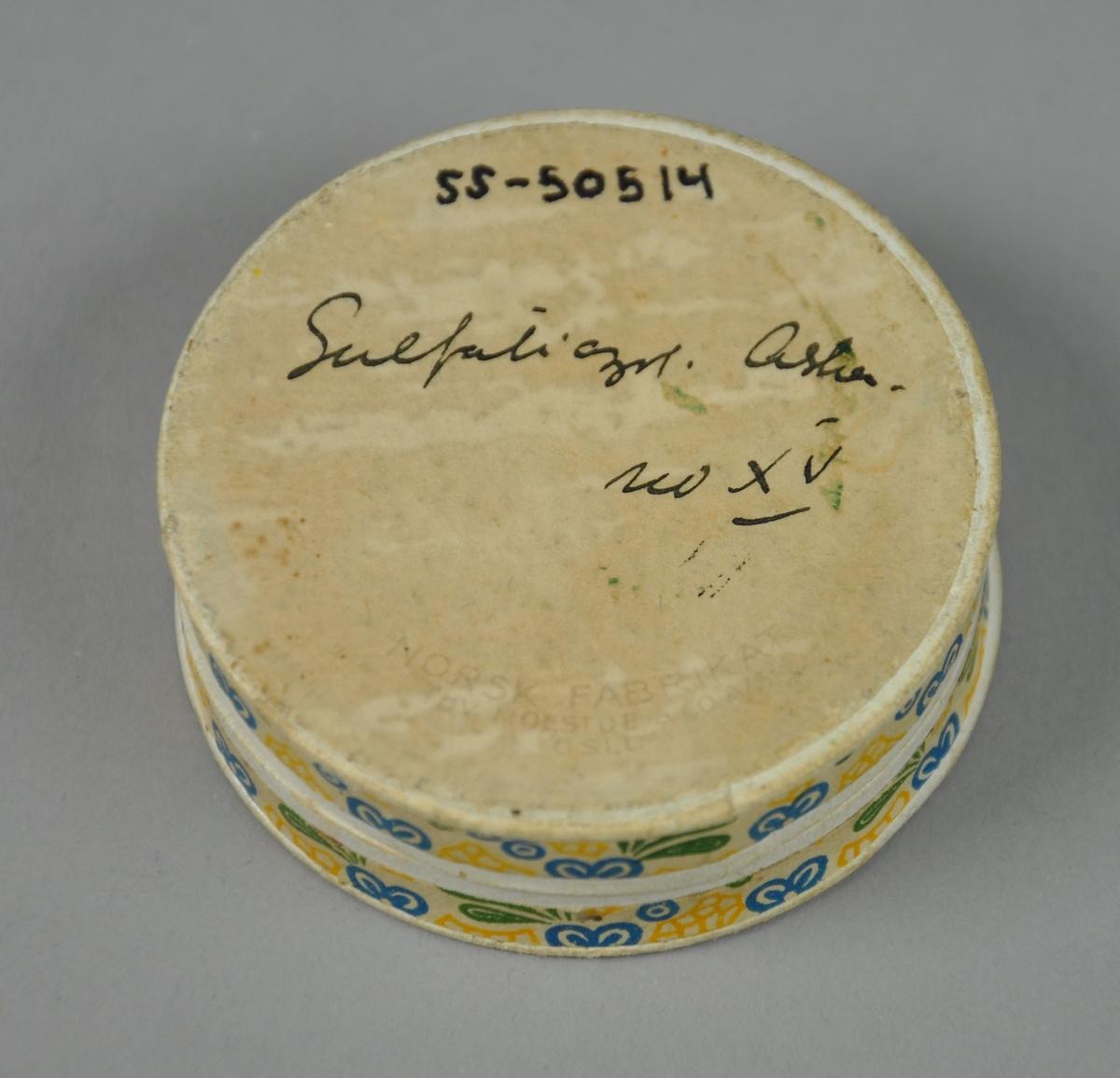 Rund pilleeske av papp i hvit farge med blå skrift, dekormønster på siden. Logoen til Brumunddal Apotek på lokket. I esken ligger en liten spiker og seks pennehoder til fyllepenn.