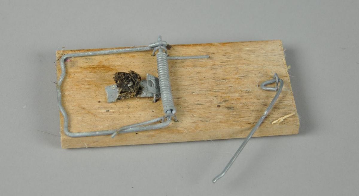 Rektangulær musefelle av tre, med låsemekanisme av metall. Ikke funksjonell.