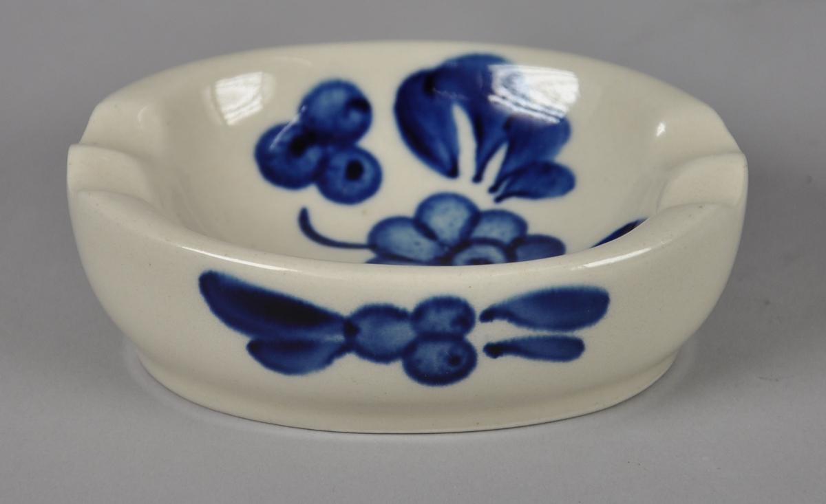 Oval sopeholder av glassert keramikk. Har malt dekor med motiv av blå blomster, blader og bær.