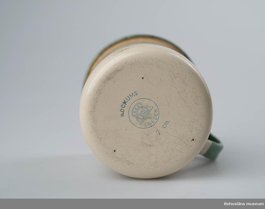 Cylinderformad mugg med handtag. Gul emalj med grön kant och handtag. Märkt med Kockums fabriksmärke i botten.