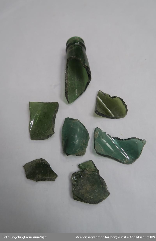 Syv fragmenter i ulike størrelser. En av fragmentene, den største, er en flasketut.