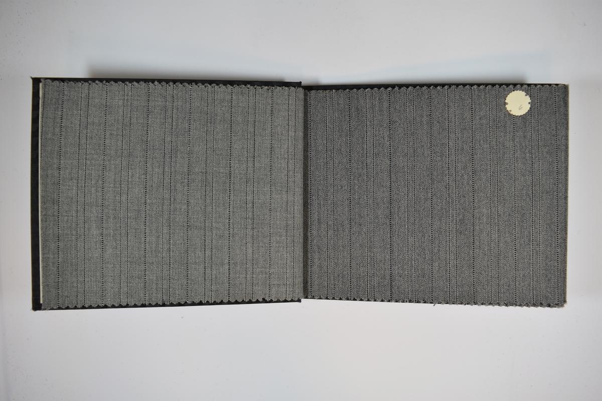 Prøvebok med 6 stoffprøver. Relativt tynne stoff med diskret striper. Vevemønsteret er likt for alle prøvene, bare fargenyansen varierer i ulike gråtoner. Stoffene ligger brettet dobbelt slik at vranga skjules. Stoffene er merket med en rund papirlapp, festet til stoffet med metallstifter, hvor nummer er påført for hånd. Innskriften på innsiden av forsideomslaget indikerer at alle stoffene har kvalitetsnummer 425.   Stoff nr.: 425/5, 425/6, 425/7, 425/8, 425/9, 425/10.